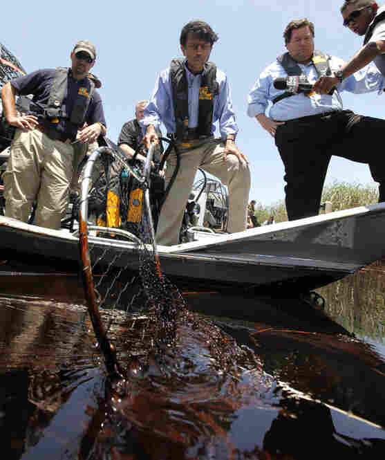 "Louisiana Gov. Bobby Jindal (center) and Plaquemines Parish President Billy Nungesser (right) tour the oil-impacted marsh of Pass a Loutre, La. ""This is the heavy oil that everyone's been fearing that is here now,"" said Jindal."