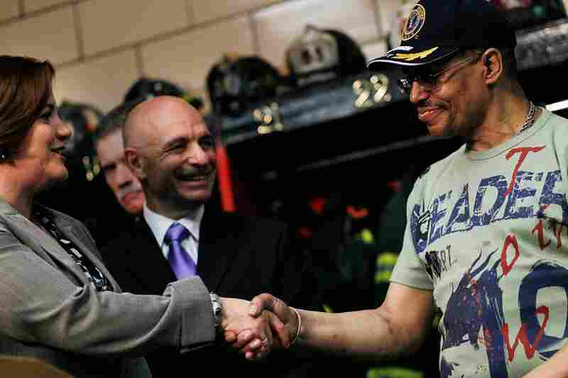 Lance Orton (right), the street vendor who alerted police to the bomb in Times Square, shakes hands with City Council Speaker Christine Quinn at a New York firehouse Tuesday. Orton is being hailed as a hero for his role in notifying the police.