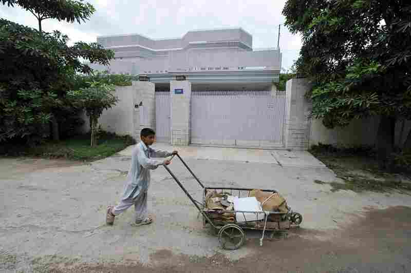 A Pakistani youth pushes his cart past the locked residence of  Shahzad in Peshawar, Pakistan, on Wednesday. Pakistan detained two people linked to the attempted car bombing and pledged to cooperate with the U.S.