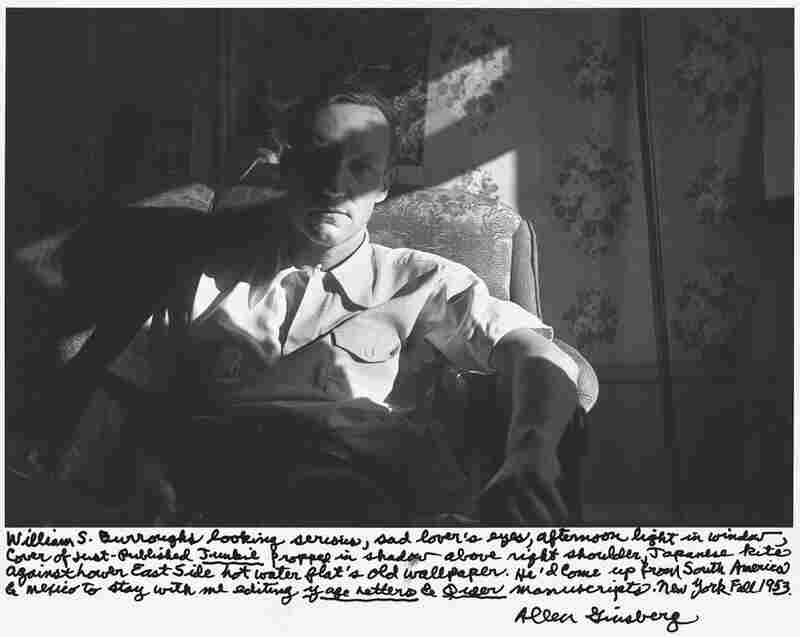 """William S. Burroughs looking serious, sad lover's eyes, afternoon light in window, cover of just-published Junkie propped in shadow above right shoulder, Japanese kite against Lower East Side hot water flat's old wallpaper. ... New York Fall 1953."""