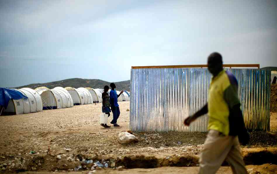 A man passes an outdoor latrine at Camp Corail, an organized relocation camp, outside Port-au-Prince, Haiti, on Tuesday.