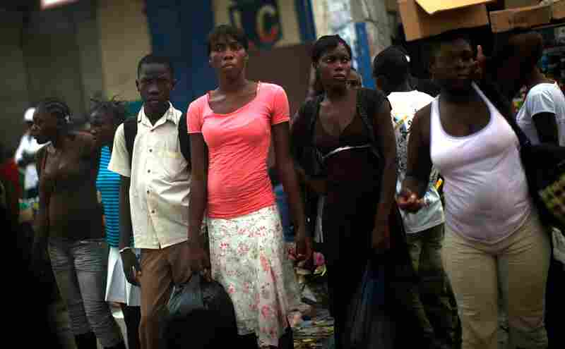 Women wait at a taxi stand in downtown Port-au-Prince. Things may be calm in Haiti, but the road to recovery still stretches ahead.