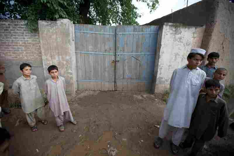 Boys stand outside the locked gates to the home in Mohib Banda the Shahzad family maintains there.  Although Faisal Shahzad never lived in the village, his family visits regularly and many people there know him.