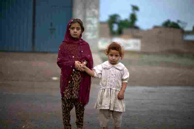 Young girls watch the mass of reporters and village elders gathered around the former mayor's house. Residents of the town expressed shock and disbelief about the allegations against 30-year-old Shahzad.