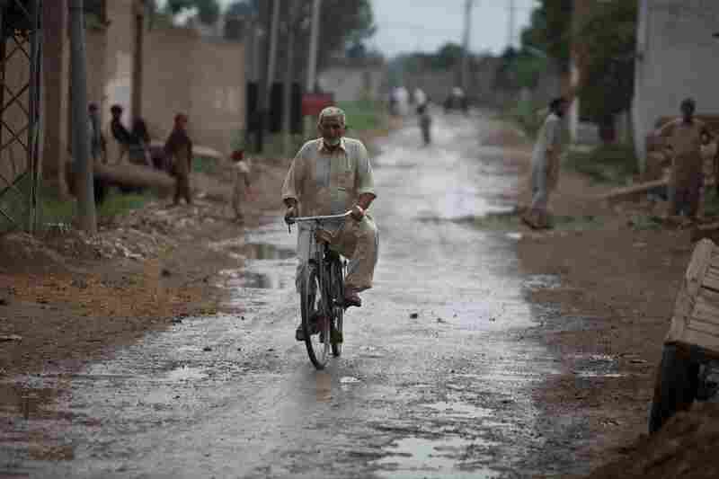 A man rides down the central road in Mohib Banda, where many people know the Shahzad family.