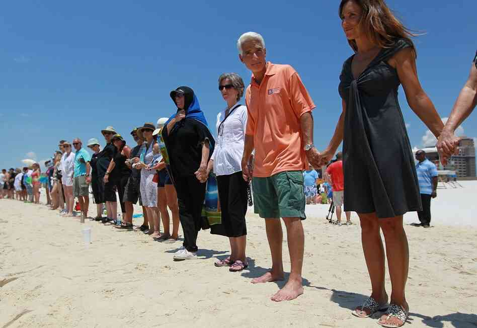 Florida Gov. Charlie Crist and wife Carole Rome Crist (right) stand with others during a Hands Across the Sand event June 26 in Pensacola, Fla. The event was staged across the nation to protest offshore oil drilling.