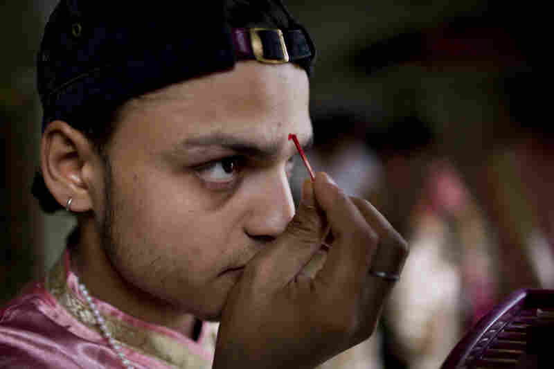 Damodar Sharma, 23, a Hindu priest, applies a bindi to his forehead before an evening ritual in the holy city of Varanasi, India. He will perform a puja, a Hindu ceremony in which priests present flowers, incense, food and other items to a murti, an image or icon of a divine spirit.
