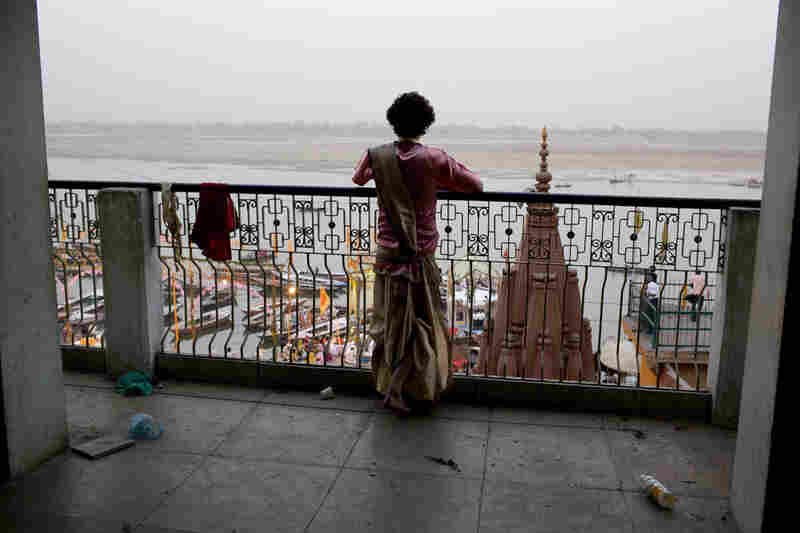 Gokul Sharma, 18, watches from a balcony overlooking the Dasaswamedh Ghat where hundreds of people gather for the puja, which is performed seven nights a week.