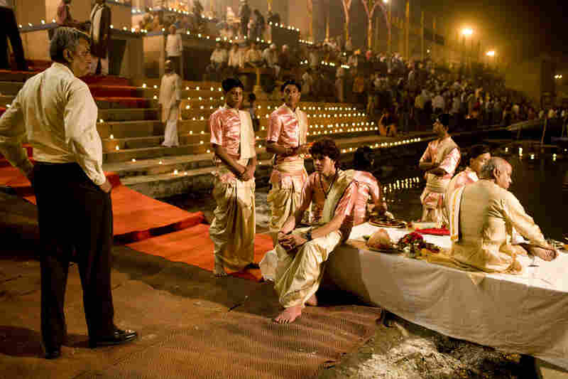 The priests wait patiently with their guru (far right) on the banks of the Ganges before the ceremony begins.