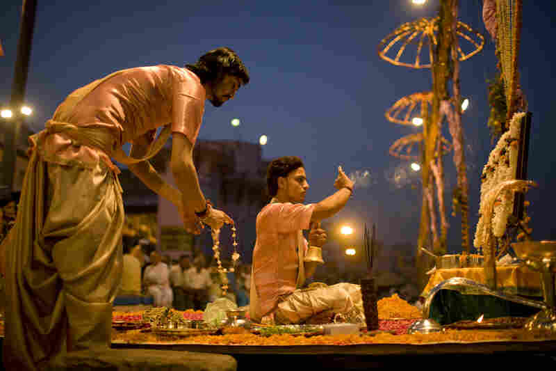 Sharma (right) and Vastoda prepare their platforms. Incense, flowers and lamps holding candles are all used to pay gratitude to Shiva, a Hindu deity, and the Ganges River.