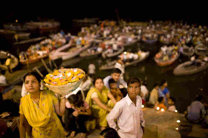A woman selling flowers and candles, used as personal offerings to the Ganges River, walks through the crowd.