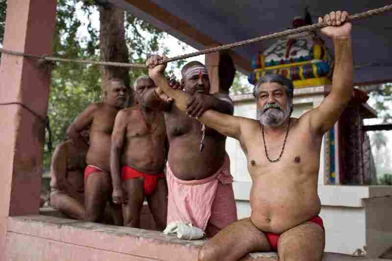 Suraj Chaurasiya rubs the arm of his guru, whom he credits with teaching him everything he knows.