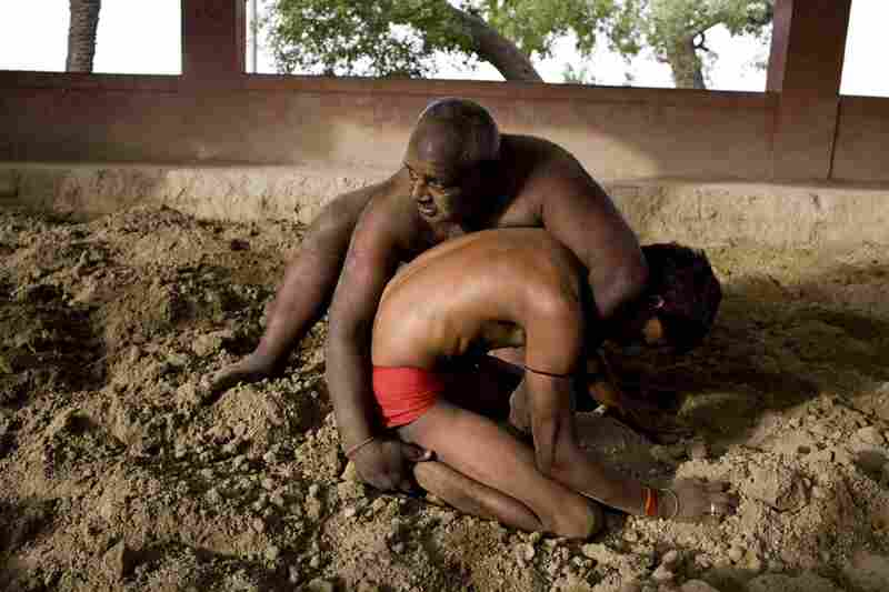 Suraj Chaurasiya (top) runs the wrestling academy. He doesn't charge his students any money. He relies on donations and whatever people leave behind. Here, he trains a young student in the wrestling pit.