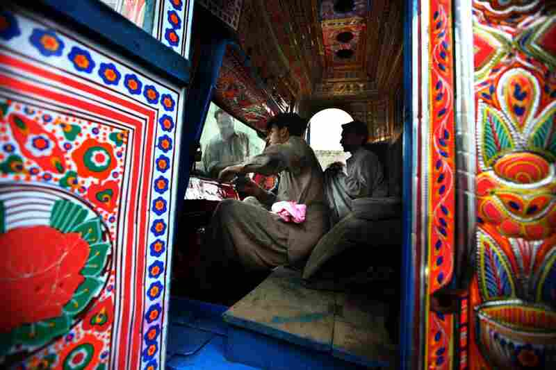 Truck art contractor Muhammad Zaman, 43, far left, washes the windshield of a newly painted truck as his workers clean its interior. Contractors coordinate all the decorating work — they line up the various craftsmen and the specific artist to paint the detail work on the trucks.