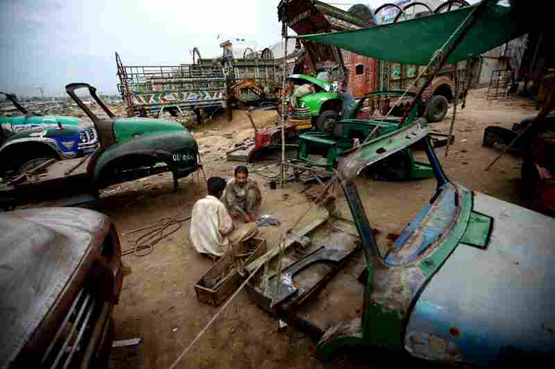 At the makeshift home of a large gathering of mechanics, welders, craftsmen, painters and metalworkers — all working on a fleet of distinctive Pakistani transport trucks — workers shape metal with hammers amid old truck cabs. In the background, mechanics work on a truck engine.