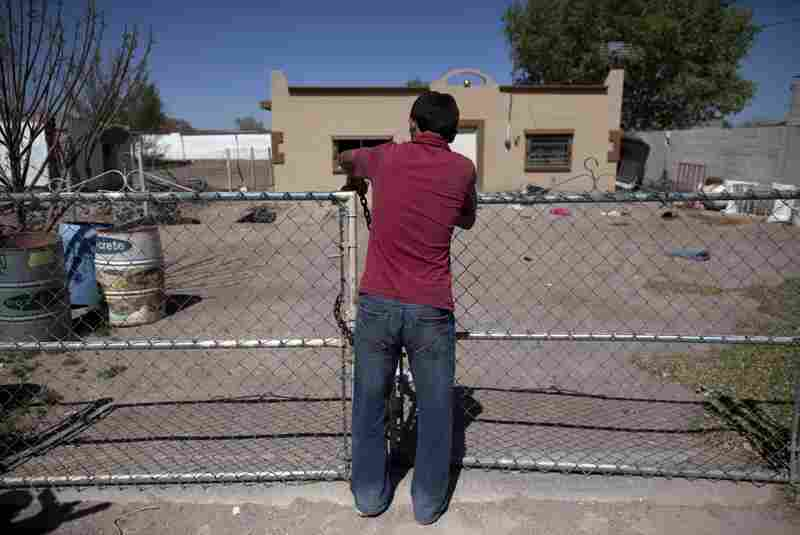 A 14-year-old boy locks the front gate of his house while fleeing El Porvenir with his family.