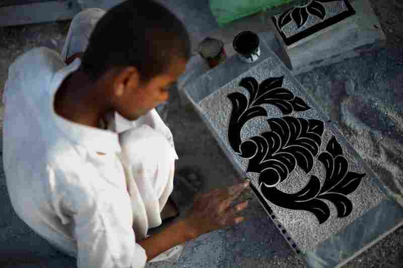 Stonecutter Raja Junaid Mahmood, 17, puts finishing touches on a gravestone in Taxila. Mahmood says he is saving his meager wages for his education — he has dreams of one day becoming an electrician.