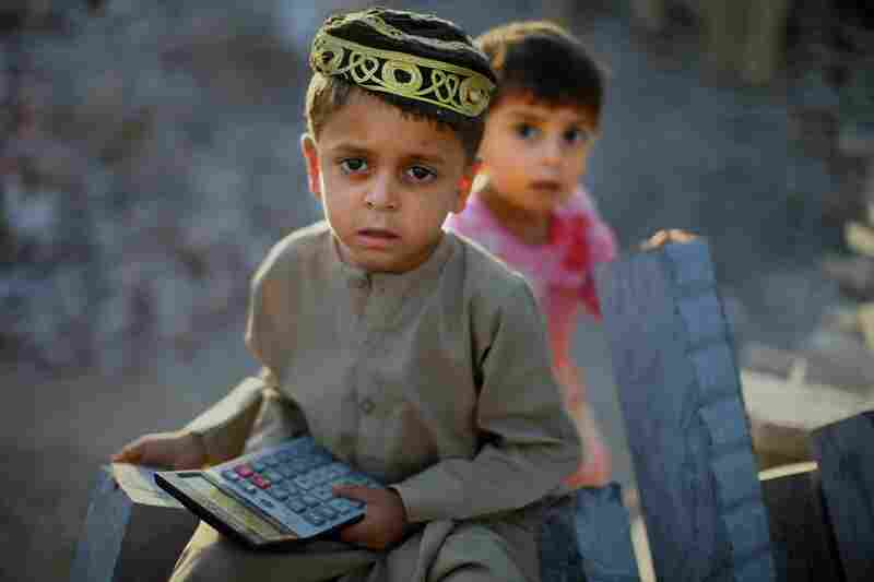 Four-year-old Abdul Wahid sits on a pile of stones with his sister at his father's stonecutting operation in Taxila. He holds a calculator, which makes sounds that he likes.