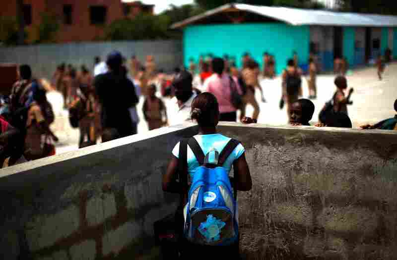 A mother watches her boy play in the courtyard of the Saint-Jean l'Evangeliste Catholic boys school in downtown Port-au-Prince. The old school was destroyed in January's earthquake, which left more than 80 percent of schools damaged or destroyed.