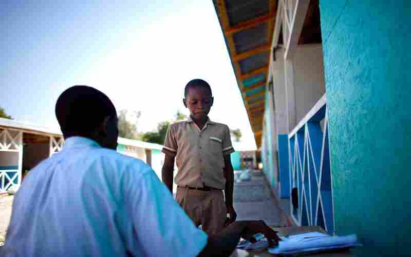 A teacher talks to a boy who had been disruptive in class.