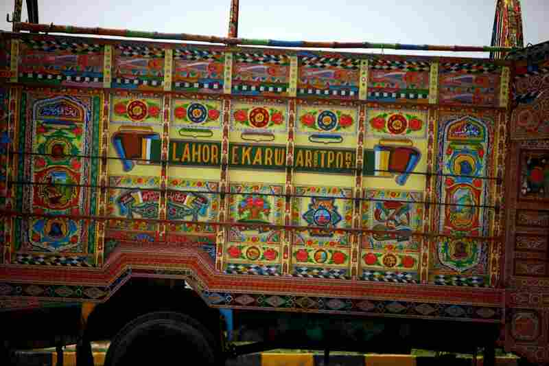 On the Pakistan side of the Wagah border crossing, a truck waits to be loaded with goods from the Indian side. Customs law mandates that all goods must be unloaded from trucks on one side of the border and reloaded onto different trucks on the other side.