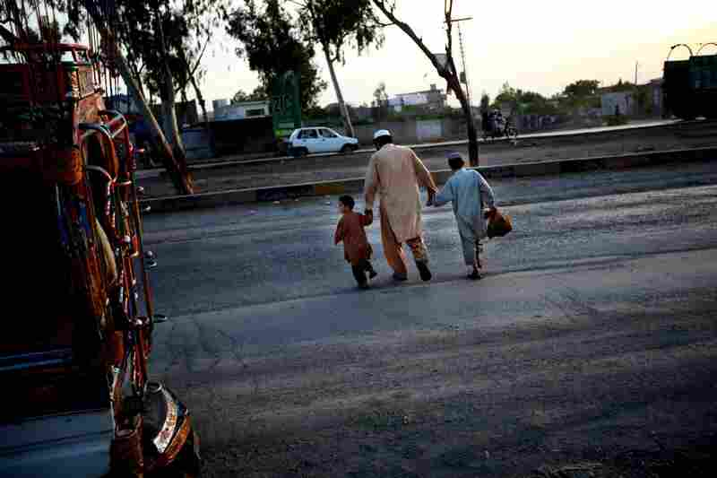 After getting off a small bus, a man leads his children across a stretch of road between Islamabad and Peshawar.