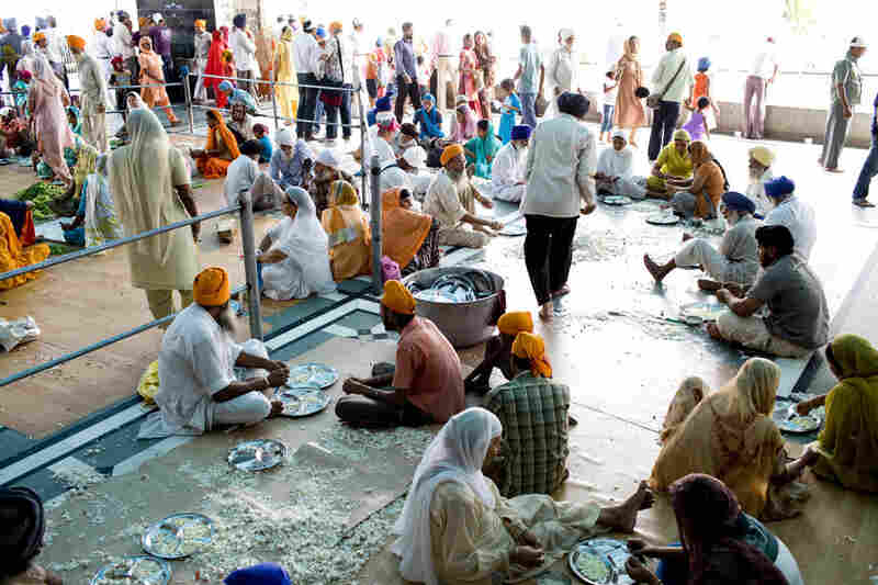 Sikhs from all over volunteer their time preparing food at the Langar. Here men and women sit together peeling garlic.