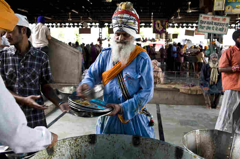 A Sikh holy man helps sort food waste from the plates before they go into the washing section.