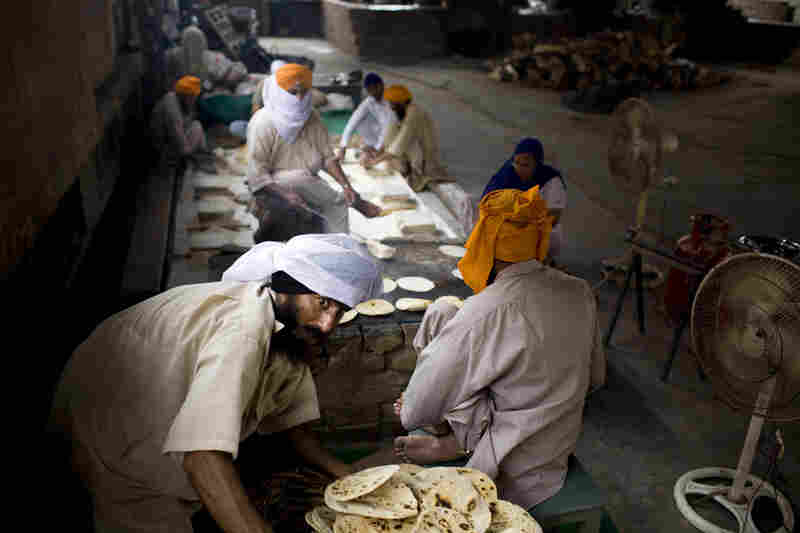 Volunteers cook and gather freshly baked chapattis inside the Langar.