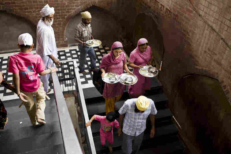 After eating their free meal, Sikhs carry their plates to be washed.