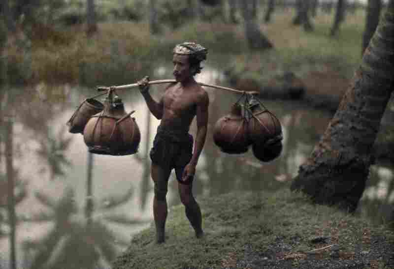 Porter with wine gourds, Bali, 1928