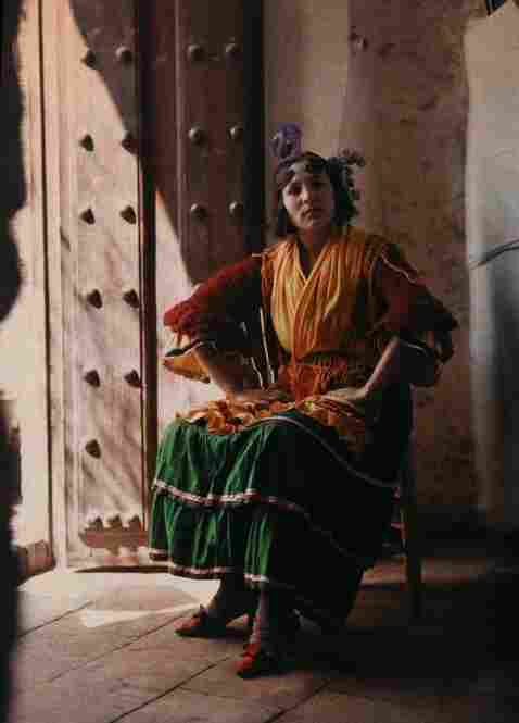A gypsy in traditional dress poses arms akimbo in a chair, Granada, Spain, published 1929
