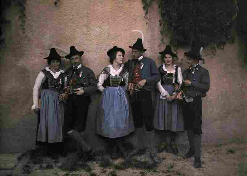 A Tyrolean singing troupe in traditional costume meets by a medieval wall, Innsbruck, Austria, published 1932