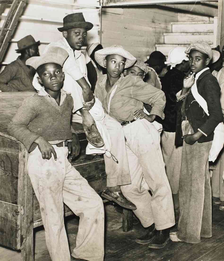 Cotton pickers wait in line to be paid in a plantation store. Mileston, Miss., 1939