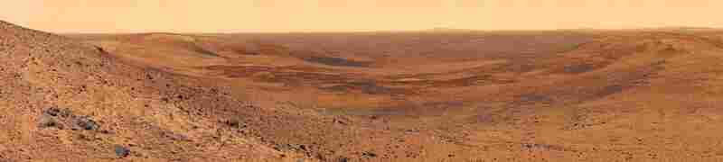 The View Of Basin To The Northeast Of Husband Hill On MarsThis view of Mars was captured by the Spirit rover, which has been roaming Mars and sending back photos and data samples since 2004. In this shot, basaltic plains stretch to the distant rim of Thira Crater. Mosaic compiled of multiple images. Spirit Rover, Nov. 3, 2005.