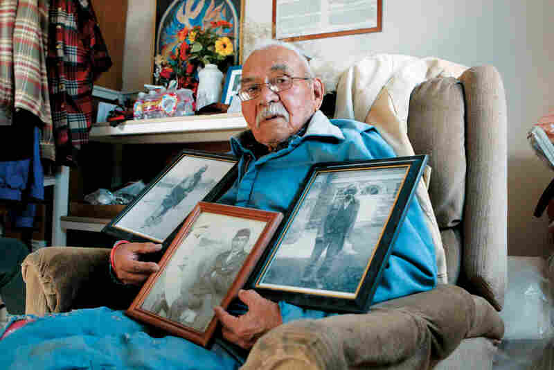 Baily Henio holds three photos. In his right hand is a photo of his warrior grandfather, Jose Pino. In the center is a photo of Henio as a young soldier during World War II. The third photo shows his father, Jake Henio.