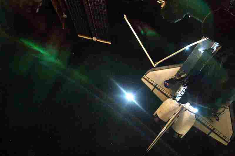 An aurora lights up the Earth's sky behind the shuttle Atlantis near the end of the orbiter's recent visit to the International Space Station.