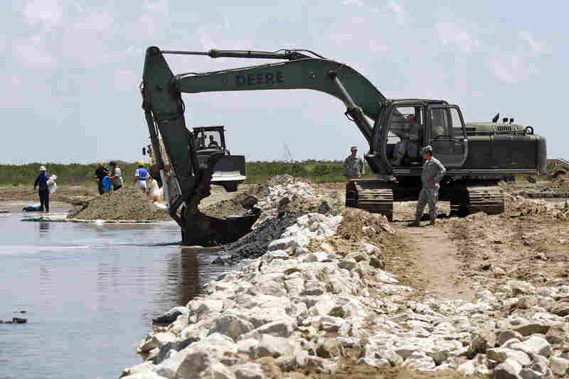 Members of the Louisiana National Guard build a land bridge at the mouth of wetlands on Elmer's Island.