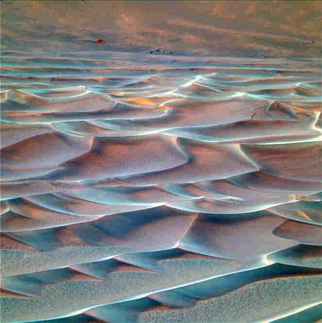 "This ""false color"" view of sand dunes at the bottom of Endurance crater is scientifically useful for distinguishing among iron-bearing minerals within the sand. The rover cameras can see farther into the ultraviolet and infrared than human eyes can. Scientists use that capability to create false color images of Martian terrain."