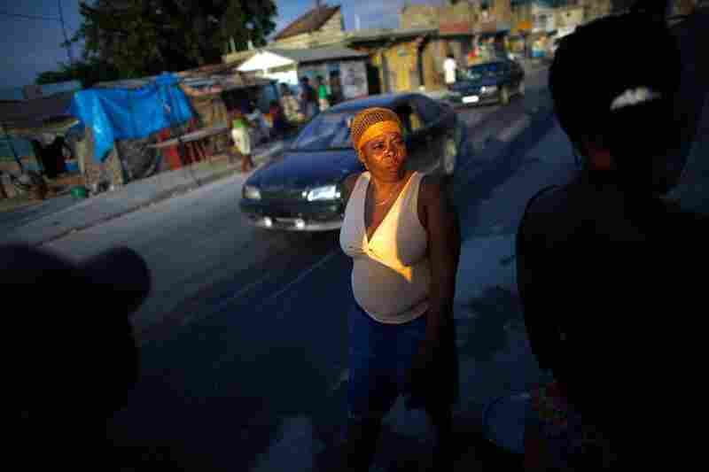 A woman walks past the camp, where Port-au-Prince meets the suburb of Carrefour. In the median, people sell food and clothing — and even moonshine at a makeshift bar — as the traffic passes.