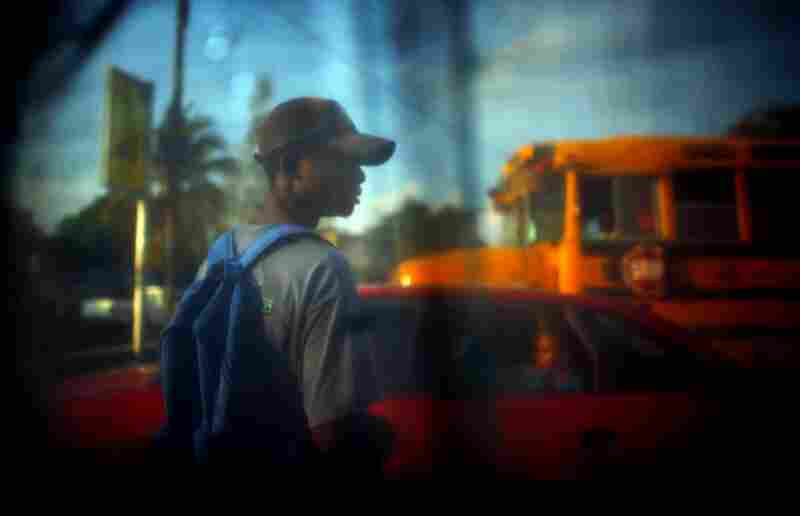 The view from inside a shelter shows a boy waiting for traffic to clear before stepping out on the highway.