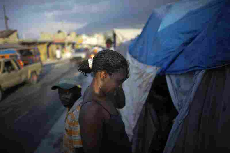A woman wipes dirt and sweat from her head before entering her tent.