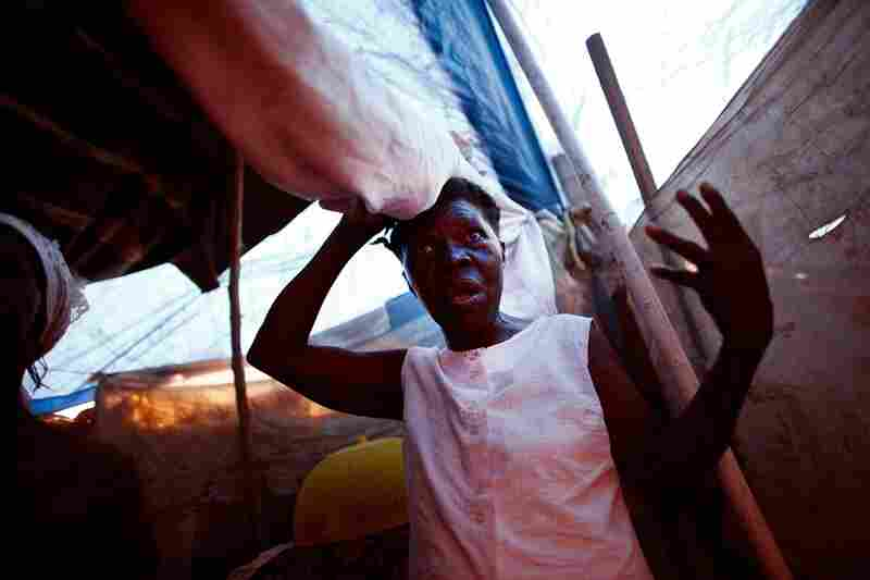 Elsie Desforttes lifts the cloth separating her tent from her neighbors. Since the earthquake, the people in this median camp have seen no sign of help from the Haitian government or foreign aid workers.