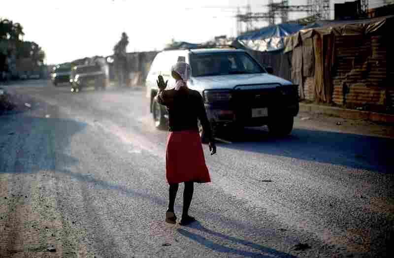 Rosemene Jean, who lost her home in January's earthquake, crosses lanes of highway traffic to get back to her home on the median. While many of the camps for displaced Haitians are at risk of flooding and disease, traffic poses the greatest danger for people living in this one.