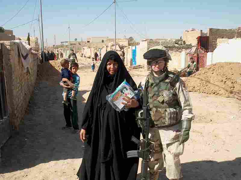 Dyarman with a local Iraqi woman while distributing food aid in October 2005. Although Dyarman has now returned to her civilian job inspecting radiological devices, colleagues say they have to cover for her mistakes.