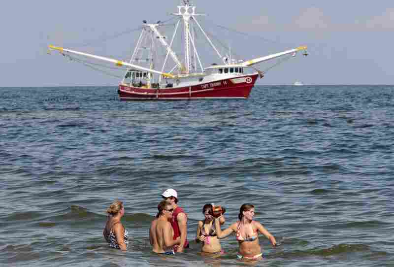 A shrimp boat skims oil from the surface of the water just off Orange Beach, Ala., as a family enjoys the surf. Oily tar balls have started washing up on Orange Beach and beaches in the western Florida panhandle.