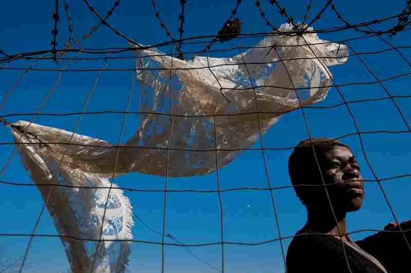 "A woman in Soweto gazes past a length of lace draped to dry on razor wire set up to deter criminals. Mandela's words after a landmark 1976 uprising against apartheid by Soweto youths still ring true: ""Much has been achieved and much remains to be done."""