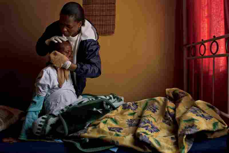 A caregiver bathes and cradles the head of a patient receiving home care from Pretoria's Thola-Ulwazi hospice, which provides free services to 700 people with AIDS and tuberculosis.