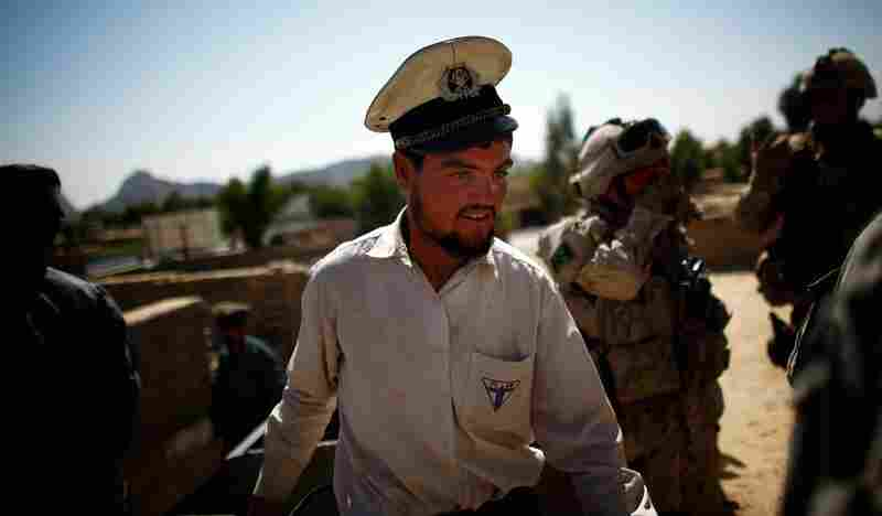 A policeman from Kandahar walks past a group of American and Canadian soldiers outside an old building that was used as a dorm for local officers. The building has no running water or electricity.