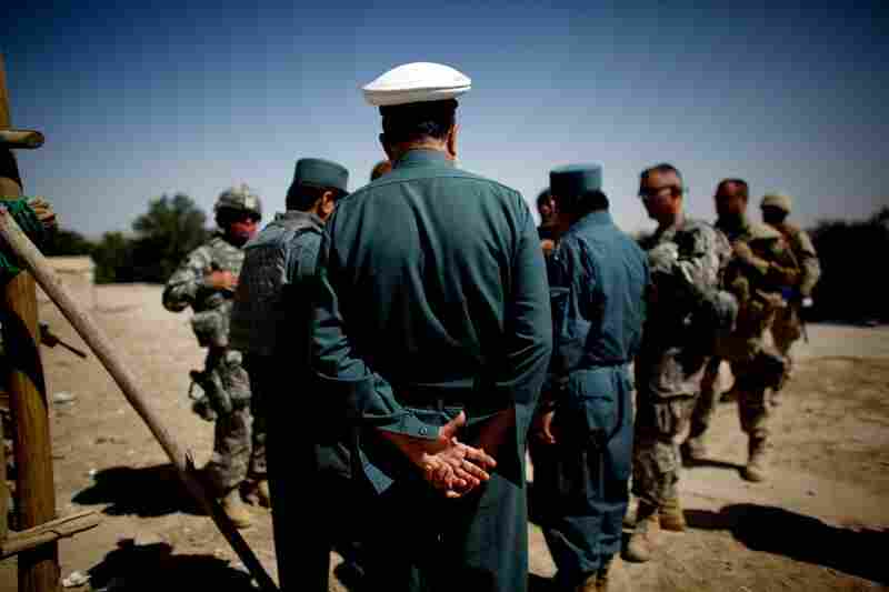 A policeman from the city of Kandahar listens to the local police chief talk with visiting U.S. and allied commanders.